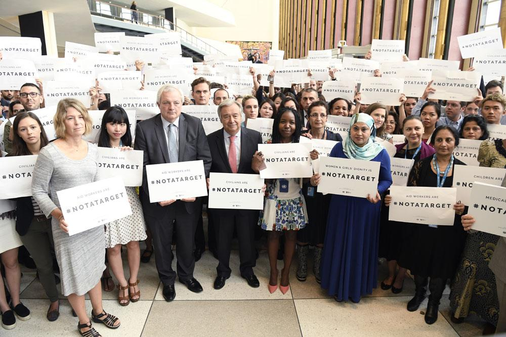 UN staff stands together marking World Humanitarian Day