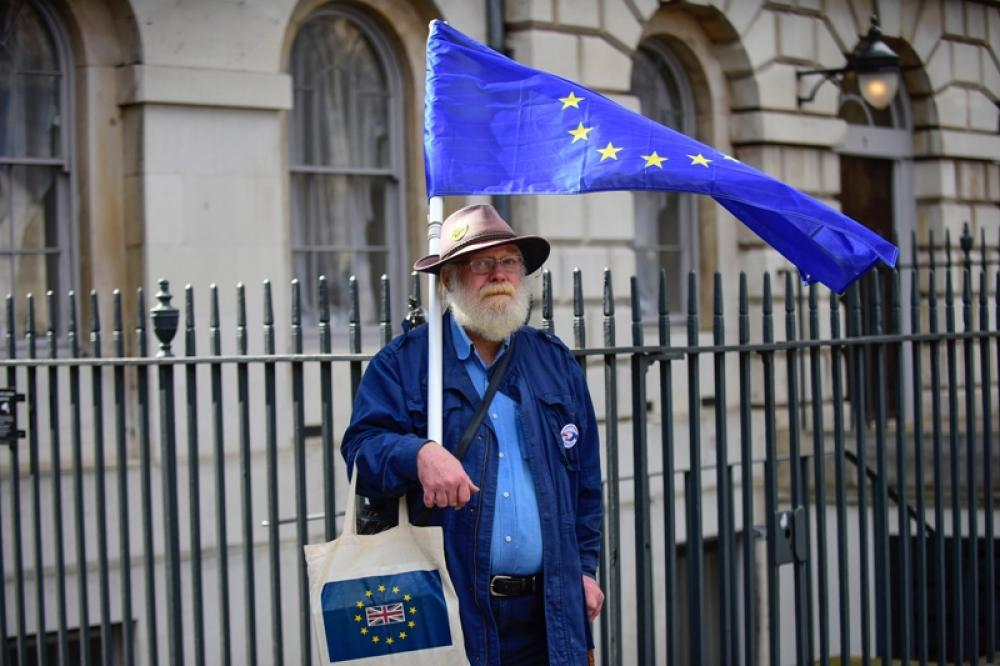 Anti-Brexit protester holds EU flag outside Parliament in London