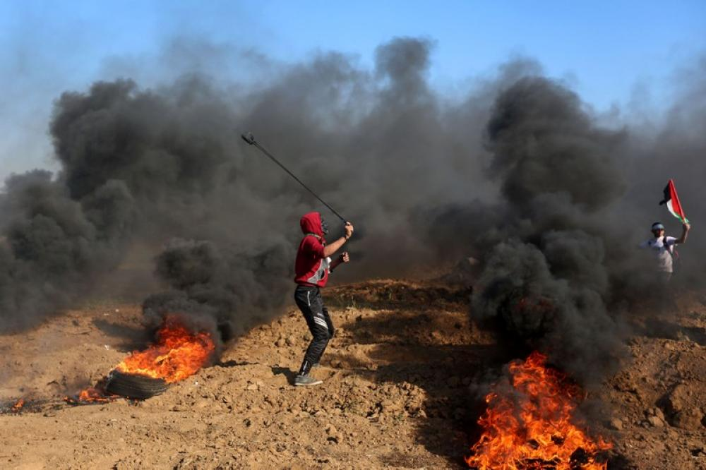 Palestinian protester hurls stones at Israeli troops