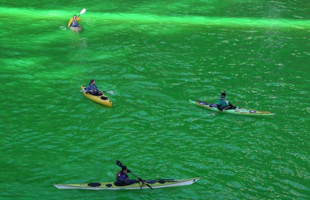 People kayak on the green Chicago River to celebrate St. Patricks Day