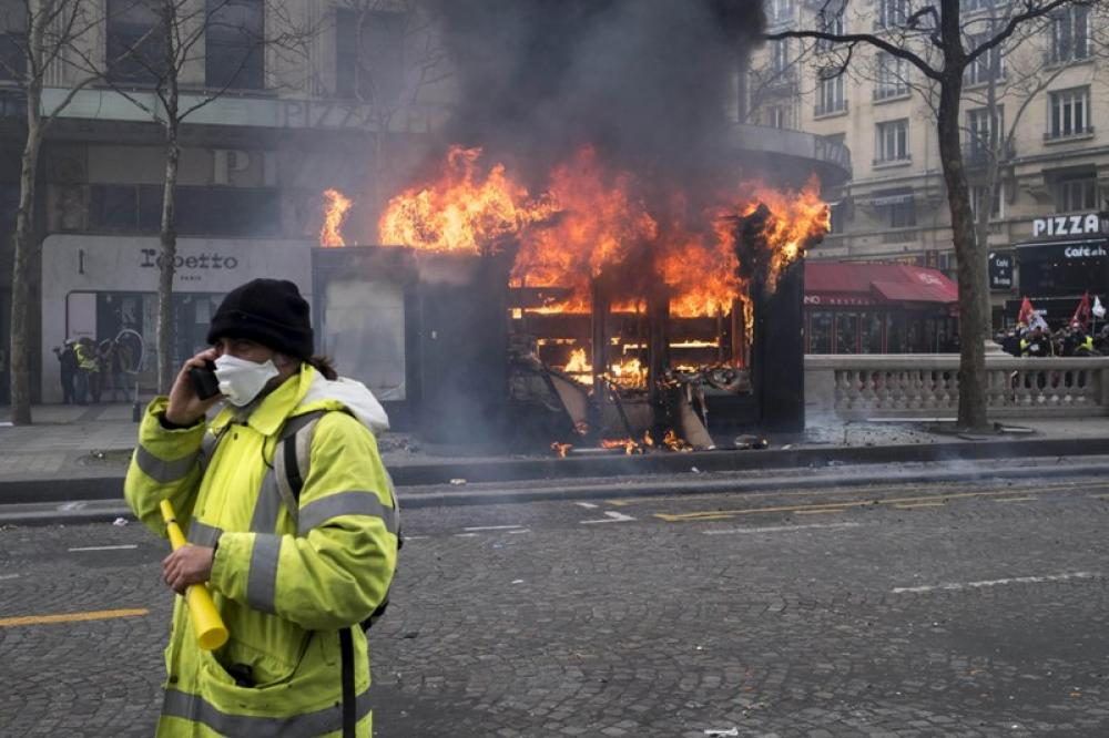 A Yellow Vest protester walks by a burning shop  in Paris