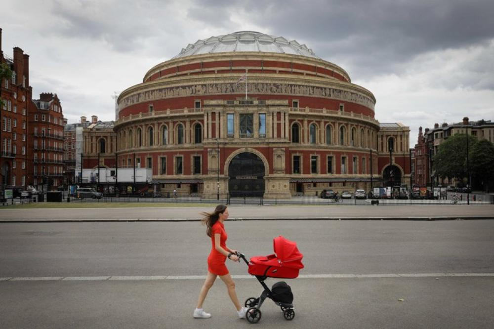 A woman walks past the Royal Albert Hall in London